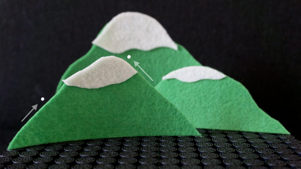 Two beads levitating above a physical model of a mountain.