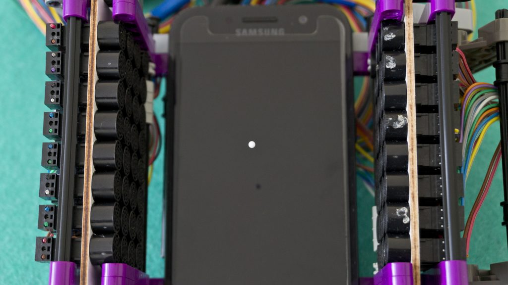 A levitating bead above a smartphone screen.