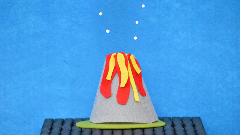 A model of a volcano with five levitating beads above it. The beads are positioned to look like ash being ejected from the top of the volcano.