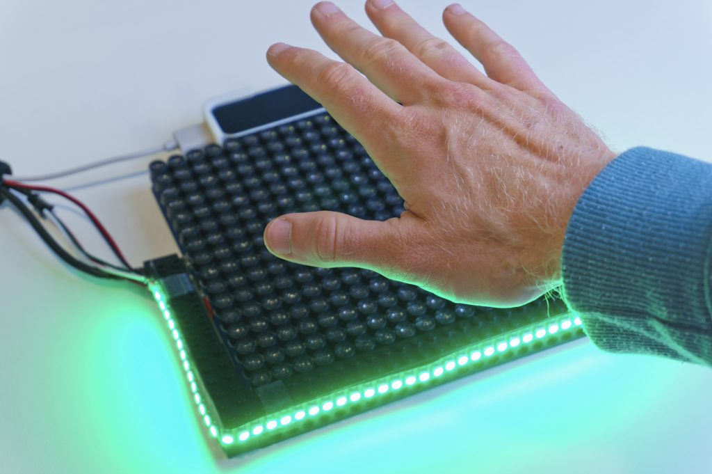 A photo of the HaptiGlow system, an ultrasound haptics device with LEDs around the front edge.