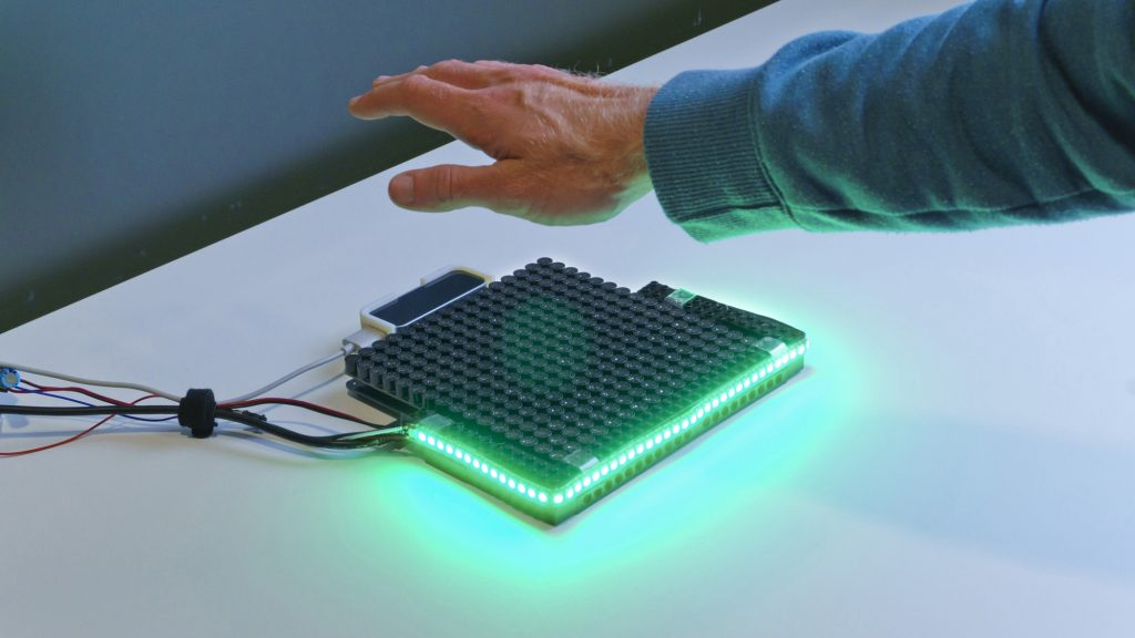 Photo of the HaptiGlow system. An Ultrahaptics UHEV1 device with a strip of LEDs around the front edge and left and right sides. The LEDs are green, indicating that the user has their hand in a good position.