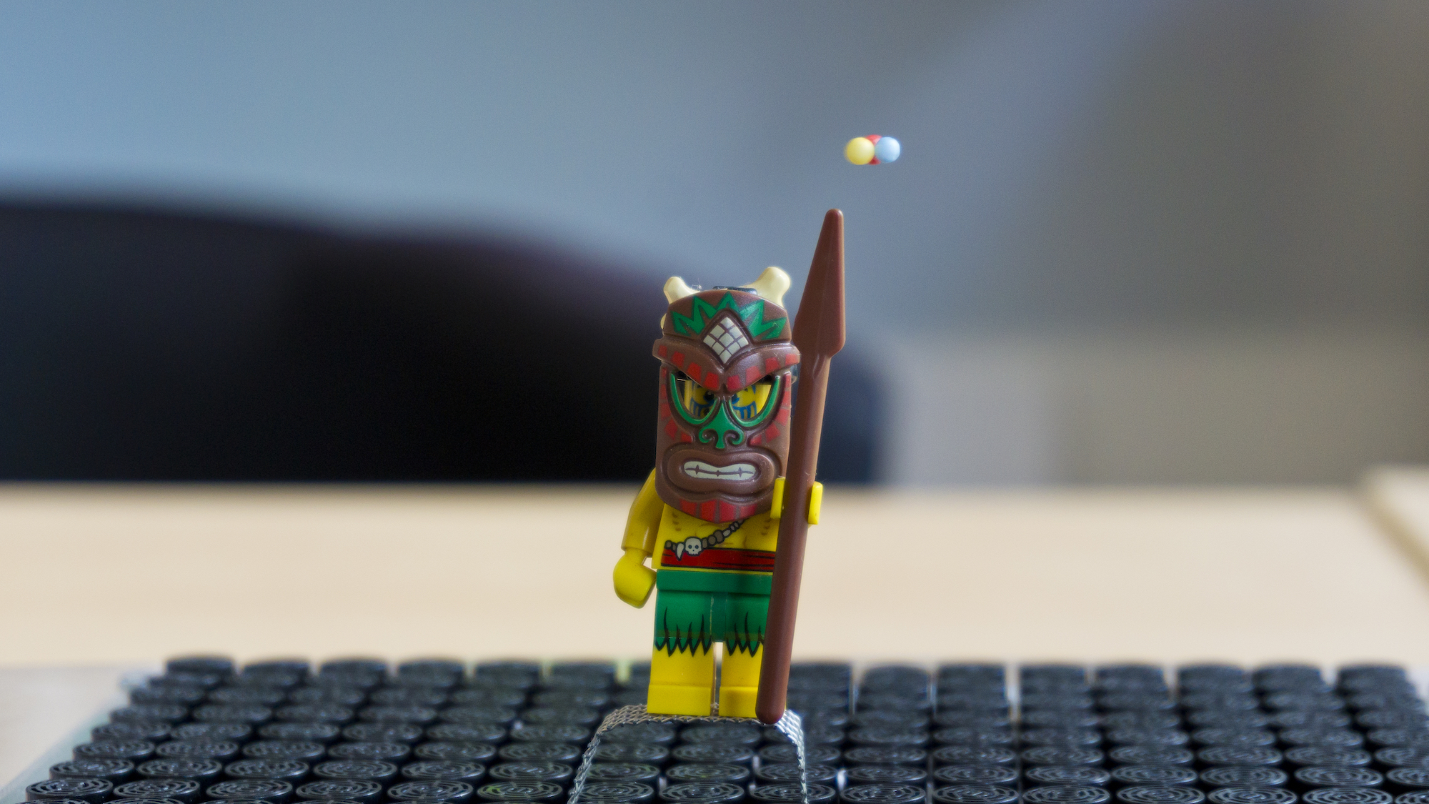 A cluster of polystyrene beads levitating above a Lego Minifigure. The miniature figure is holding a magical staff, so the beads create the appearance of magical forces being emitted by the staff.